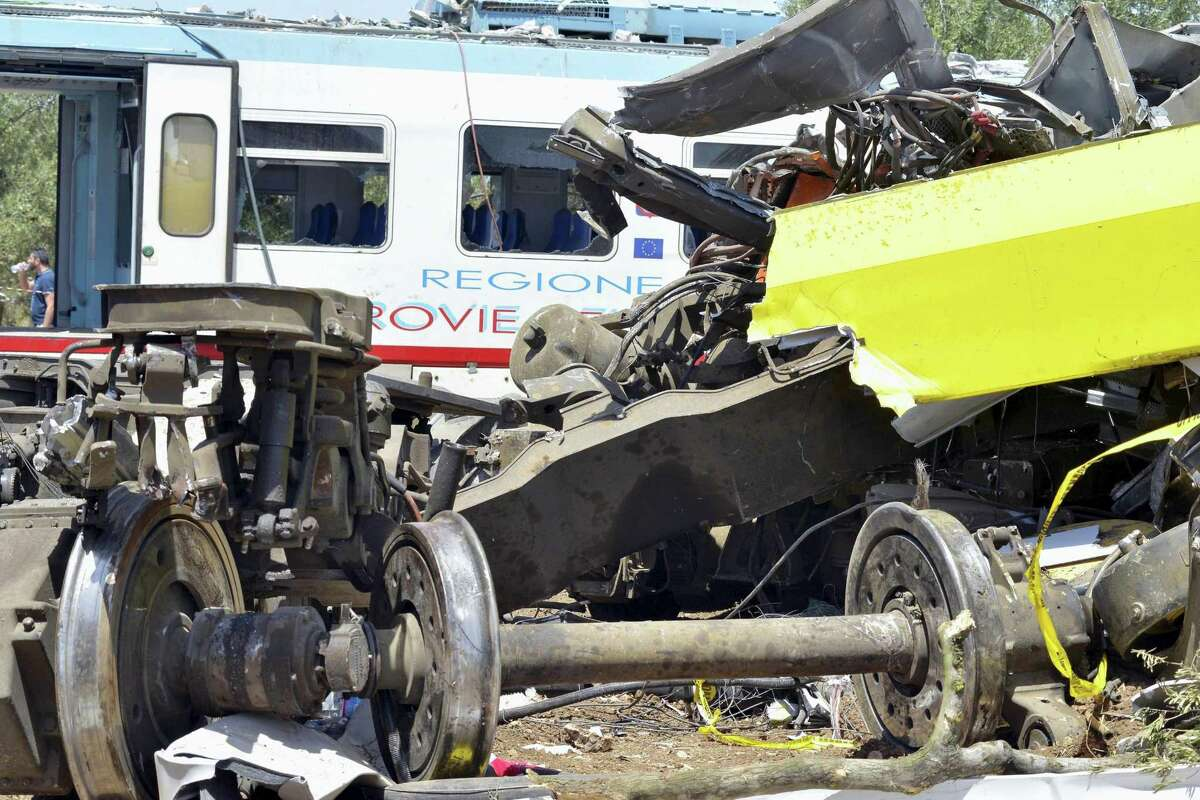 The wreckage of a carriage lies on a field near the railroad as recovery operations continued a day after two commuter trains slammed into one another just before noon Tuesday in Puglia, between the towns of Corato and Andria, Italy, Wednesday, July 13, 2016. Delayed rail improvements and the antiquated telephone alert system will be considered as part of the investigation into the violent head-on train crash in southern Italy that killed nearly two dozen people, officials said Wednesday.