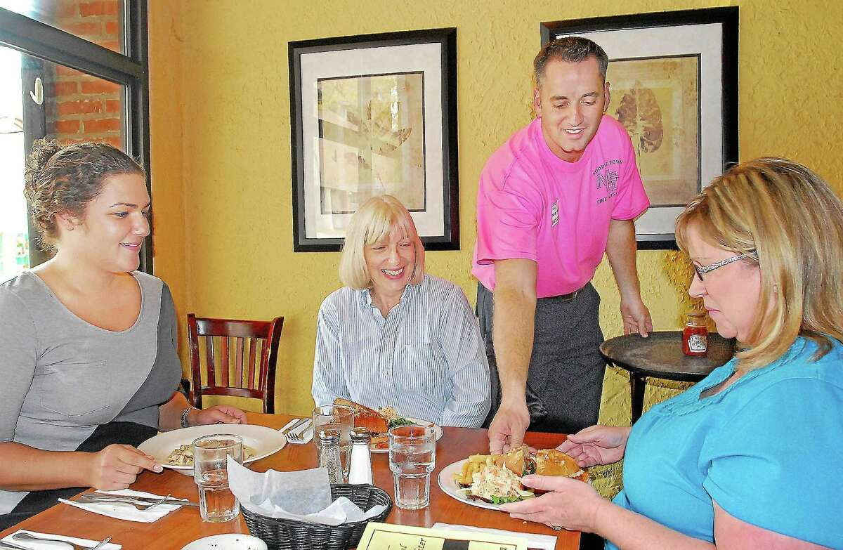 In this archive photograph, firefighter Brian France serves lunch during Tip-A-Firefighter at Tuscany Grill on College Street in Middletown.