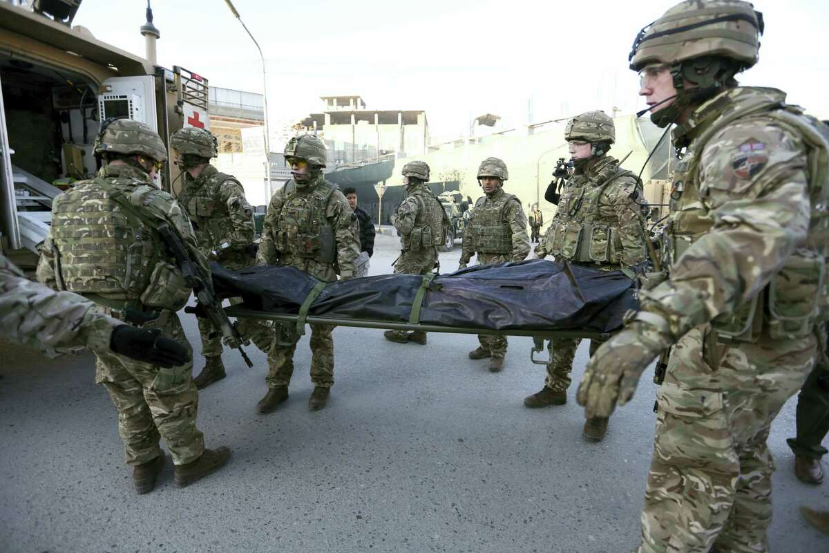 """In this Dec. 12, 2015 photo, British soldiers carry the dead body of a victim of an attack that happened near Spanish Embassy in Kabul, Afghanistan. Afghan forces are struggling to man the front lines against a resurgent Taliban, in part because of untold numbers of """"ghost"""" troops who are paid salaries but only exist on paper."""