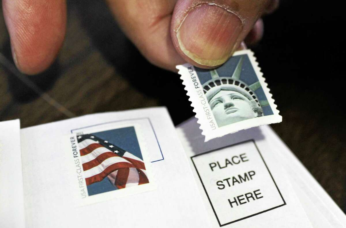 FILE - In this Dec. 5, 2011, photo, a customer places first class stamps on envelopes at a U.S. Post Office in San Jose, Calif. It'll cost another penny to mail a letter in 2013. The cash-strapped U.S. Postal Service said Thursday that it will raise postage rates on Jan. 27, including a 1-cent increase in the cost of first-class mail to 46 cents.