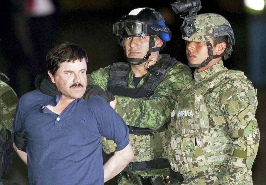 """Joaquin """"El Chapo"""" Guzman is made to face the press as he is escorted to a helicopter in handcuffs by Mexican soldiers and marines at a federal hangar in Mexico City, Mexico on Jan. 8, 2016. Mexican President Enrique Pena Nieto announced that Guzman had been recaptured six months after escaping from a maximum security prison. Photo: AP Photo/Eduardo Verdugo  / AP"""
