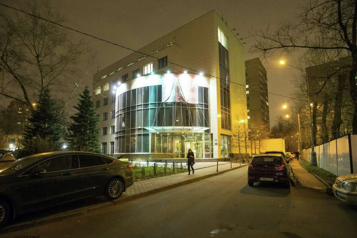 """In this November 9, 2015, file photo a woman walks from the entrance of National anti-doping agency, RUSADA in Moscow, Russia. The IOC """"would not hesitate"""" to retest drug samples from the 2014 Winter Games in Sochi if there is evidence that doping controls were manipulated, according to the Olympic body's medical director."""