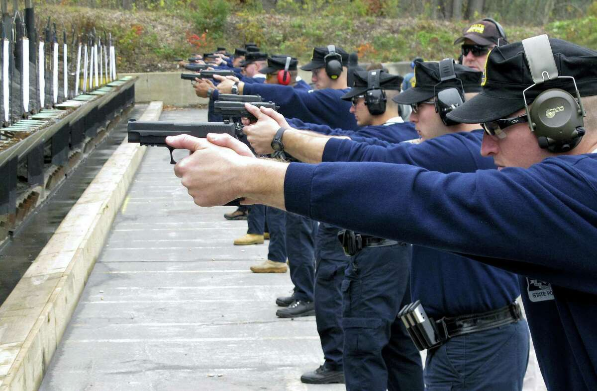 """In this file photo, Connecticut State Police recruits practice with their new .45-caliber Sig Sauer pistols during a """"dry fire"""" exercise at the state police firing range in Simsbury, Conn. Some police departments are relaxing age-old standards for accepting recruits. The changes are designed to deal with decreased interest in a job that offers low pay, rigorous physical demands and the possibility of death, all while under public scrutiny. There's also the need to lure more minorities. The Connecticut State Police is among the agencies wrestling with diversity."""