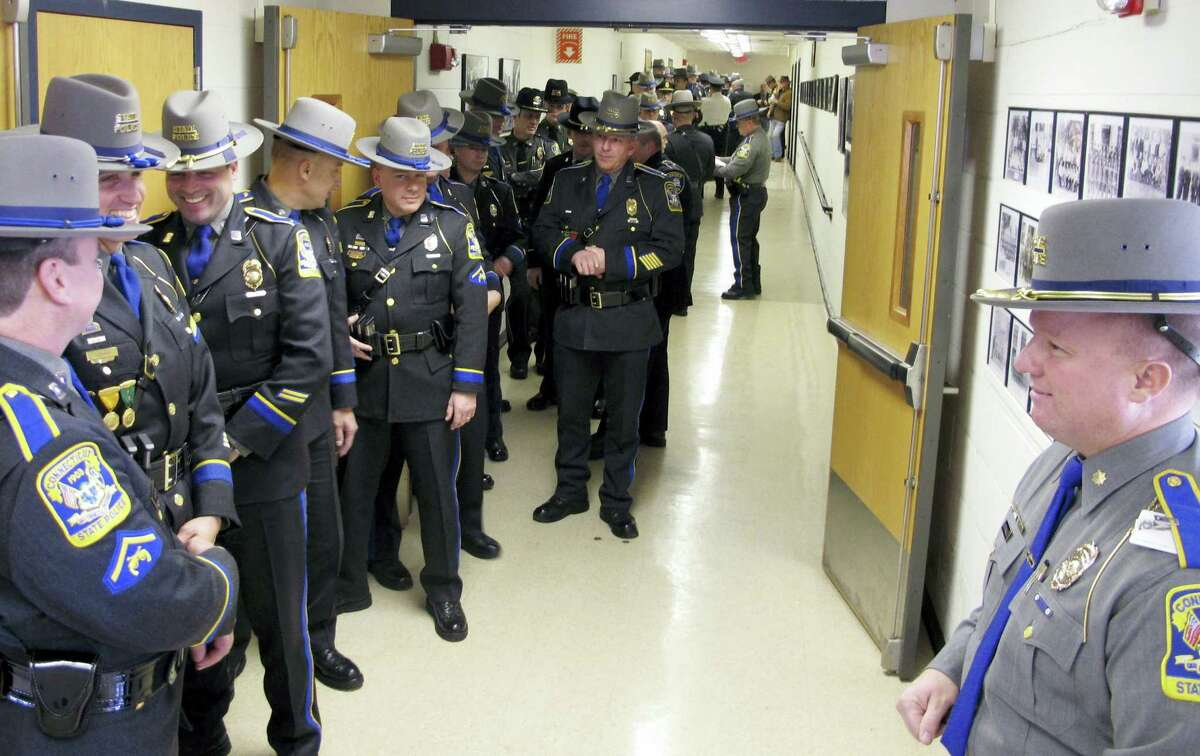 In this file photo, state and local police officers line up outside an auditorium prior to an awards ceremony at the Connecticut State Police Training Academy in Meriden, Conn. Some police departments are relaxing age-old standards for accepting recruits. The changes are designed to deal with decreased interest in a job that offers low pay, rigorous physical demands and the possibility of death, all while under public scrutiny. There's also the need to lure more minorities. The Connecticut State Police is among the agencies wrestling with diversity.