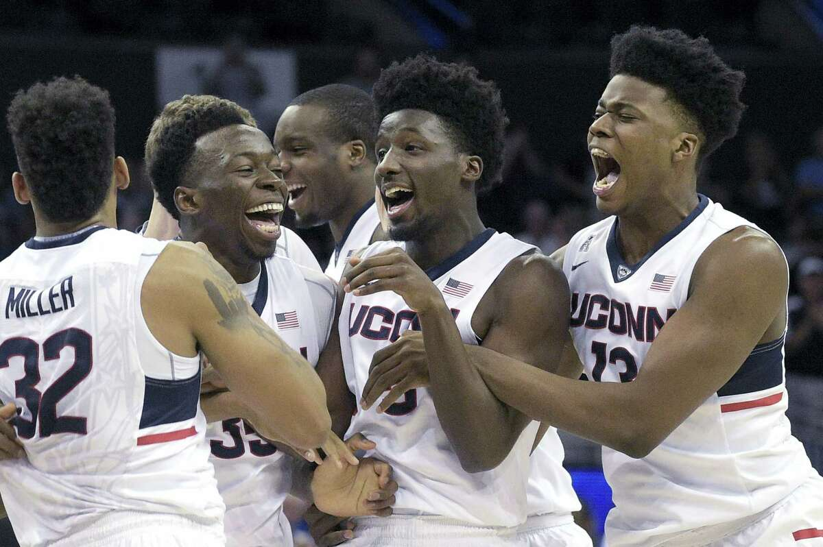 UConn forward Shonn Miller (32), center Amida Brimah (35), guard Daniel Hamilton (5) and forward Steven Enoch (13) celebrate after defeating Memphis 72-58 in the championship game the American Athletic Conference tournament in Orlando, Fla., Sunday.