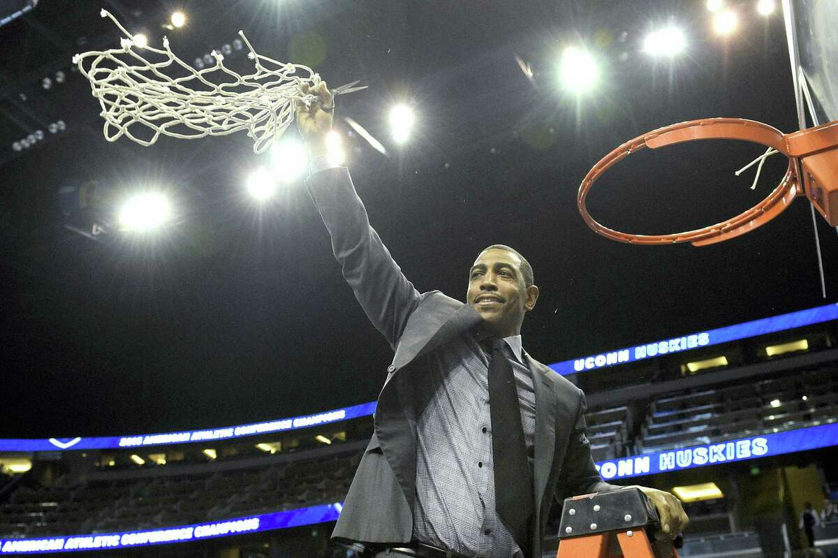 UConn head coach Kevin Ollie waves the net after cutting it from the rim to celebrate the Huskies' AAC tournament title.