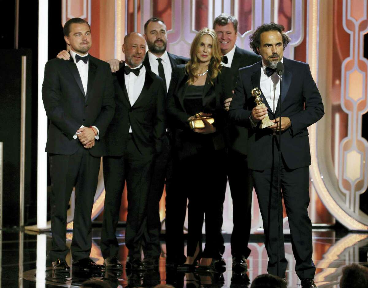 """In this image released by NBC, Leonardo DiCaprio, left, looks on with the crew of """"The Revenant,"""" as director Alejandro G. Inarritu, right, accepts the award for best motion picture drama during the 73rd Annual Golden Globe Awards at the Beverly Hilton Hotel in Beverly Hills, Calif., on Sunday, Jan. 10, 2016. (Paul Drinkwater/NBC via AP)"""