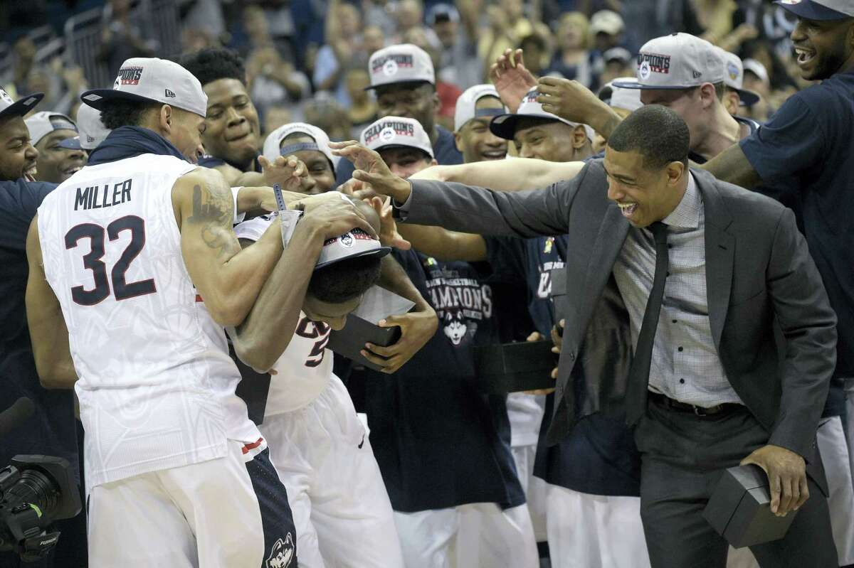 UConn guard Daniel Hamilton (5), center, is congratulated by forward Shonn Miller (32) and head coach Kevin Ollie, right, after being named the AAC tournament MVP. Hamilton and the Huskies face Colorado in the first round of the NCAA tournament Thursday.