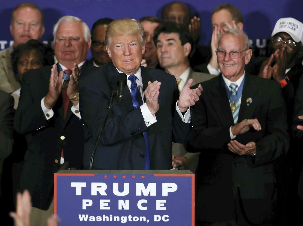 Republican presidential candidate Donald Trump leads the crowd in an applause, recognizing a Gold Star mother in the crowd during a gathering with military leaders and veterans at the new Trump International Hotel in Washington, Friday, Sept. 16, 2016.