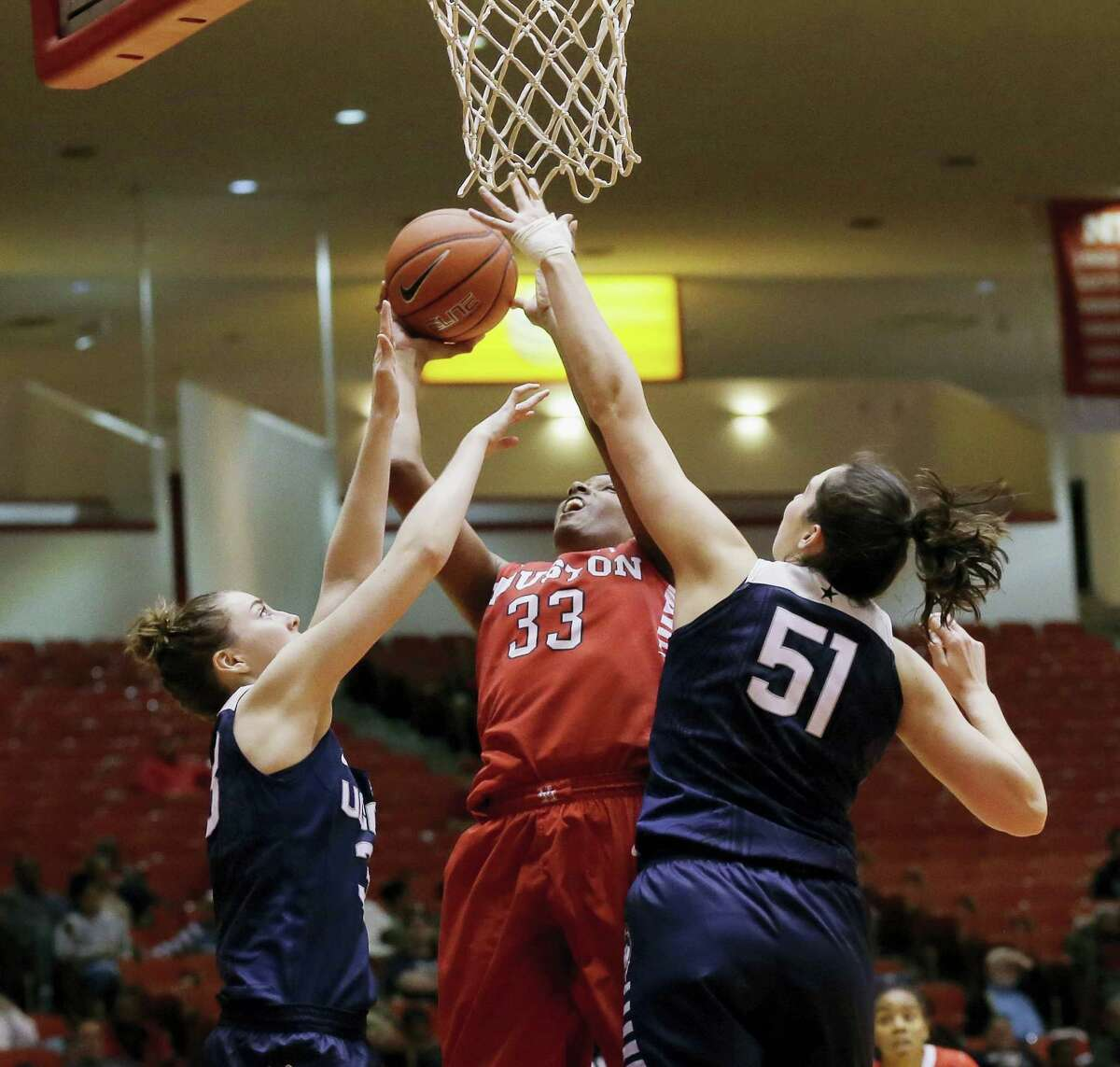 Houston forward Tyler Gilbert (33) shoots over Connecticut guard/forward Katie Lou Samuelson, left, and center Natalie Butler (51) during the second half of an NCAA college basketball game Friday, Jan. 8, 2016, in Houston. Connecticut won 76-37.