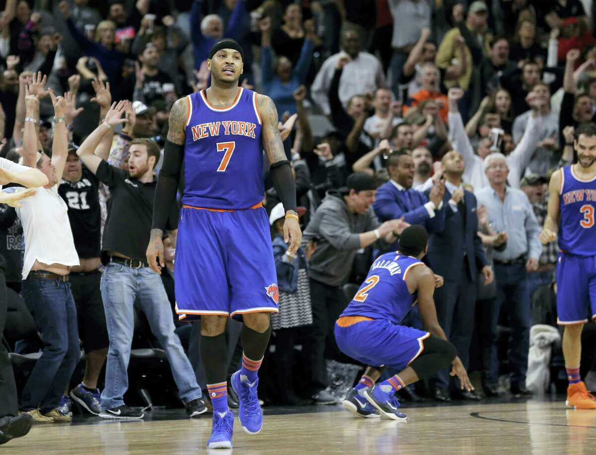 New York Knicks forward Carmelo Anthony (7) walks off the court after teammate Jose Calderon (3) missed a last-second shoot against the San Antonio Spurs during the second half of an NBA basketball game Friday, Jan. 8, 2016, in San Antonio. San Antonio won 100-99. (AP Photo/Eric Gay)