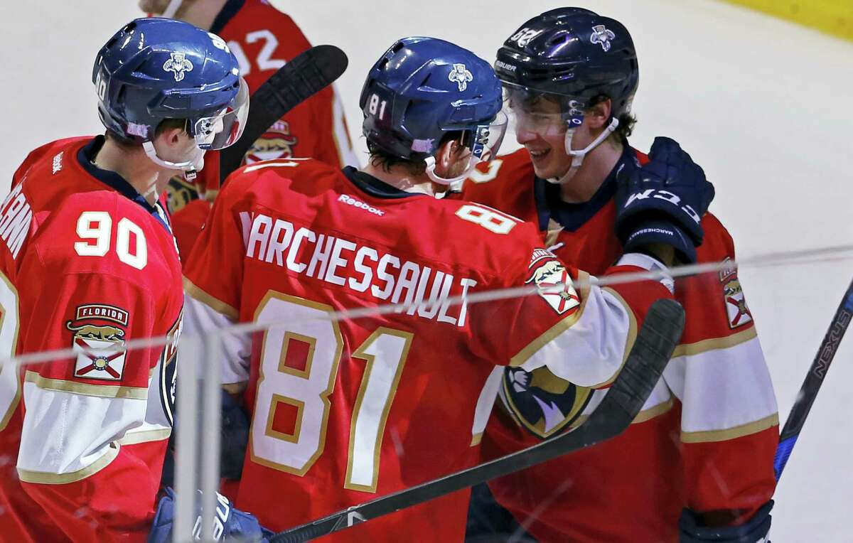 Florida Panthers center Jonathan Marchessault (81) celebrates with teammate Denis Malgin (62) who scored the winning goal in overtime to defeat the New York Islanders in an NHL hockey game, Saturday, Nov. 12, 2016, in Sunrise, Fla. Panthers center Jared McCann (90) looks on. (AP Photo/Joe Skipper)