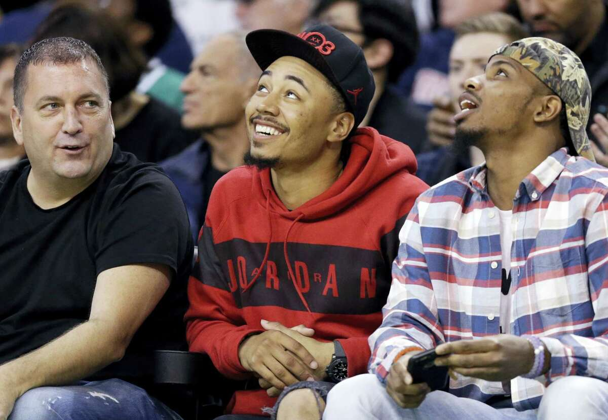Boston Red Sox baseball player Mookie Betts, center, sits courtside in the first quarter of an NBA basketball game between the Boston Celtics and the New York Knicks, Friday, Nov. 11, 2016, in Boston. (AP Photo/Elise Amendola)