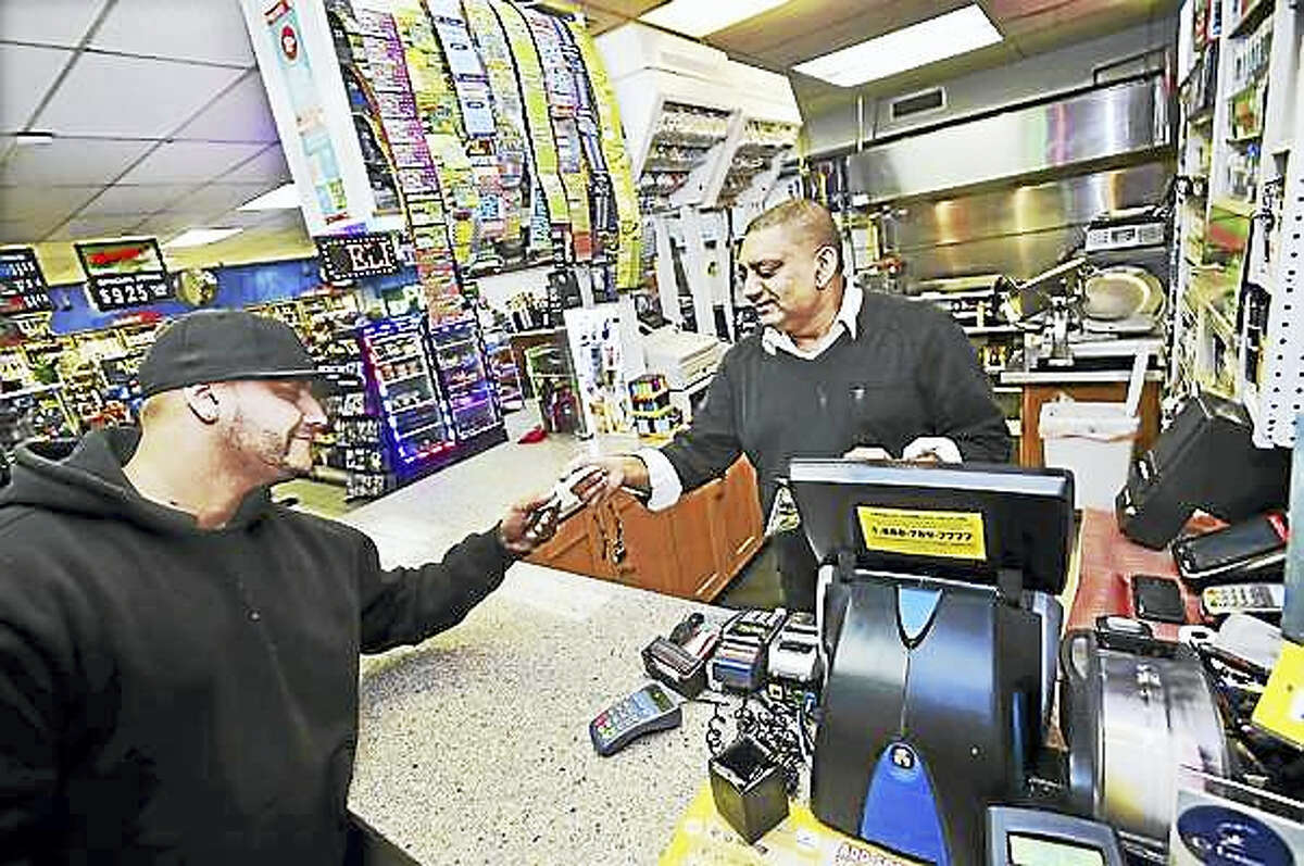 Nick Sarwar, who owns S&B Food Mart & Deli with his wife, Samina Bashir, hands a Powerball ticket to Billy Revis of New Haven Thursday night.