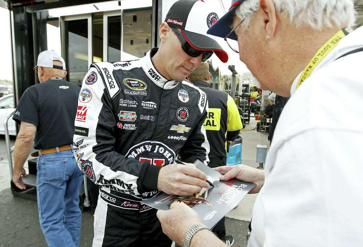 Kevin Harvick, left, signs autographs for fans in the garage area before practice at Phoenix International Raceway on Friday.