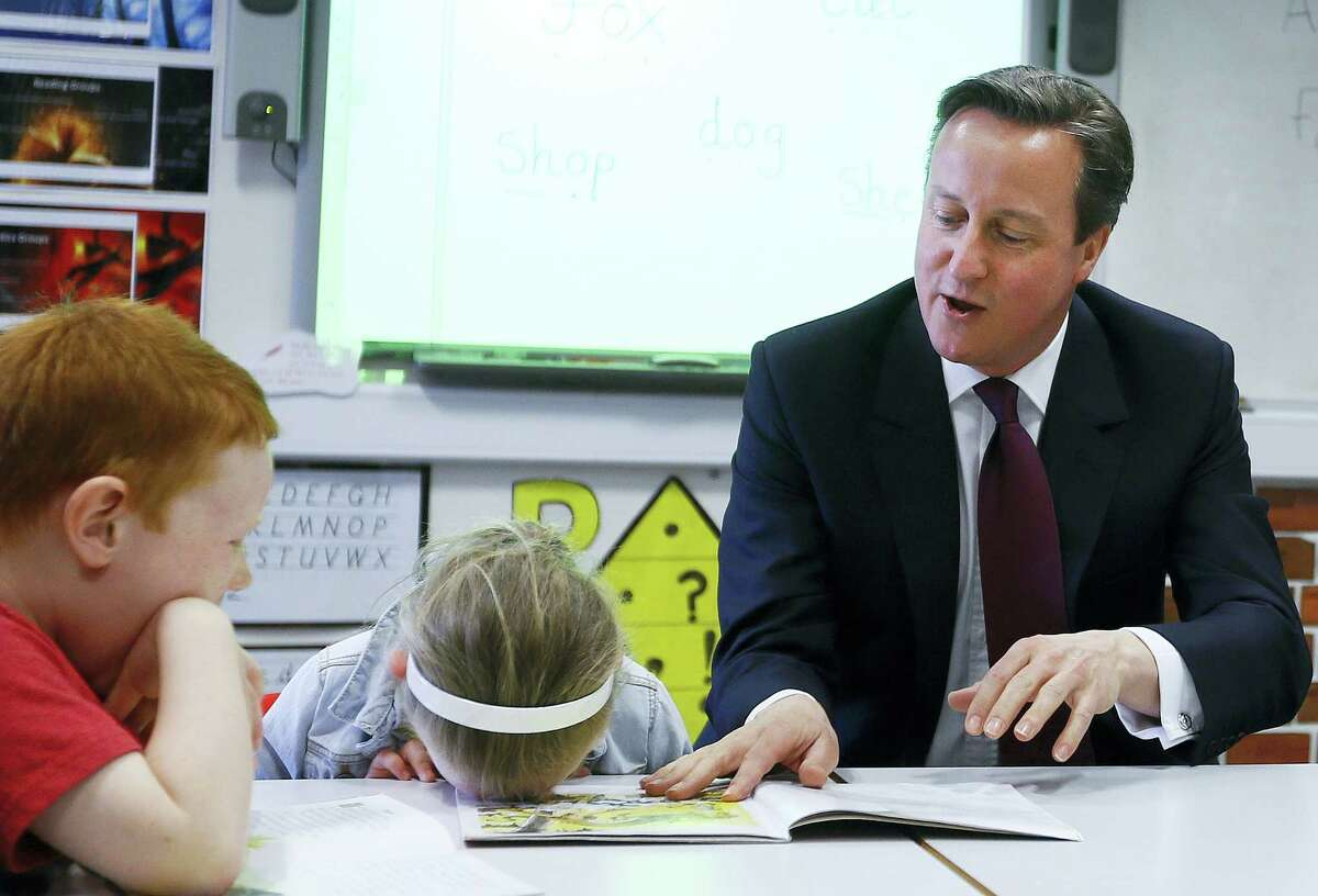 """In this Wednesday, April 8, 2015, file photo Britain's Prime Minister David Cameron reads a book to Lucy Howarth, 6, and Will Spibey, 5, left, during a visit to Sacred Heart RC primary school in Westhoughton near Bolton, England. When Cameron was elected leader of Britain's Conservative Party, the press called him the """"heir to Blair."""" Like Labour premier Tony Blair, he was a young leader who dragged his sometimes reluctant party toward the political center. Cameron steps down Wednesday, July 13, 2016, after six years as prime minister."""