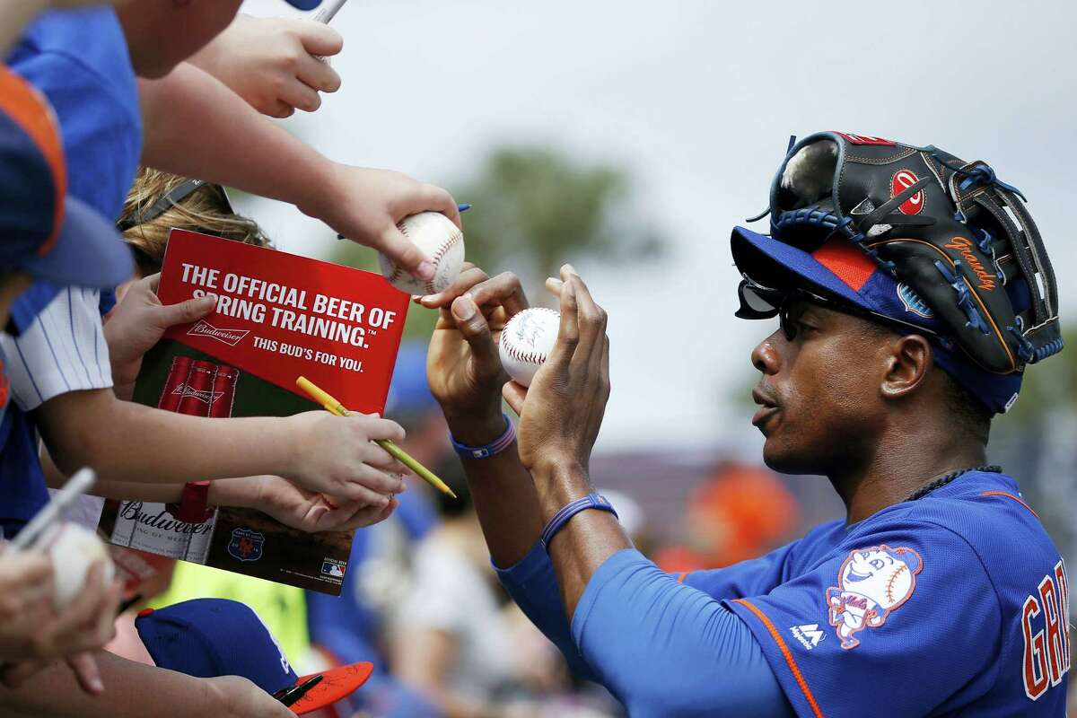 Mets' right fielder Curtis Granderson sign autographs before an Saturday's exhibition game against the Cardinals.