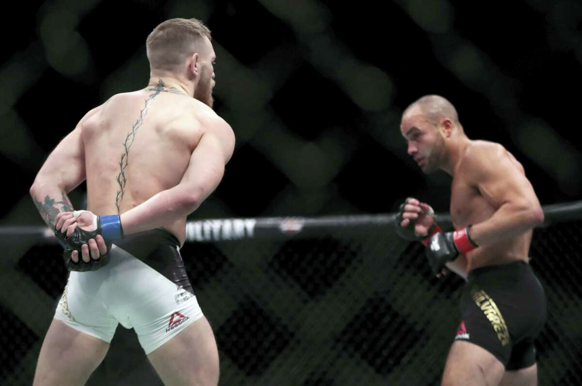 Conor McGregor, left, taunts Eddie Alvarez during a lightweight title mixed martial arts bout at UFC 205 early Sunday, Nov. 13, 2016 at Madison Square Garden in New York. McGregor won the bout.
