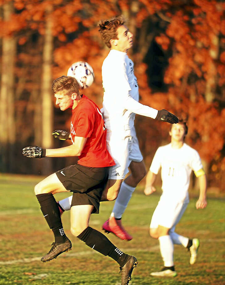 Cromwell senior Jake Pendl and Coventry junior Mason Danielson converge on the ball during Saturday's Class S quarterfinal matchup. Photo: Jimmy Zanor - The Middletown Press