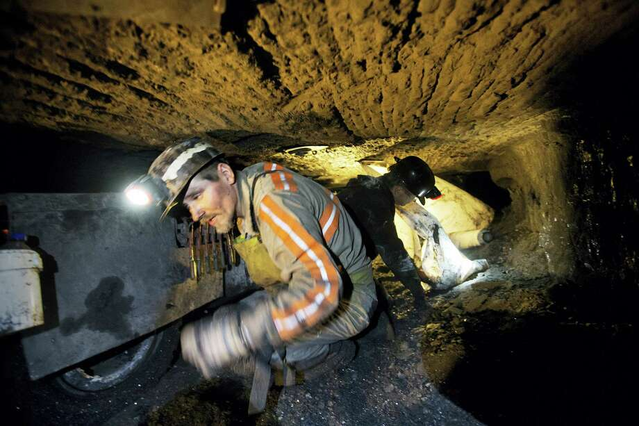 Scottie Stinson, a coal miner of 16 years, crawls through a coal mine roughly 40 inches high while securing the roof with bolts in Welch, W.Va. Coal will not go completely away anytime soon, it's the cheapest way to bring electricity to the 1.3 billion people who lack access to it, and even developed nations will still need to burn it as they transition to cleaner fuels. The carbon in coal will still be needed to mix with iron to make steel. But there is so much more coal than the world needs that only the cheapest global producers will survive. Photo: David Goldman — The Associated Press  / AP
