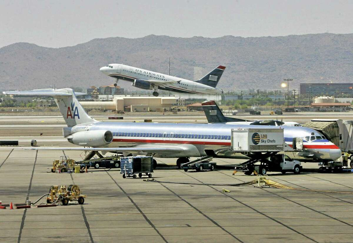 In this June 23, 2008, file photo, a US Airways jet takes-off as an American Airlines Jet is prepped for takeoff at Sky Harbor International Airport in Phoenix.