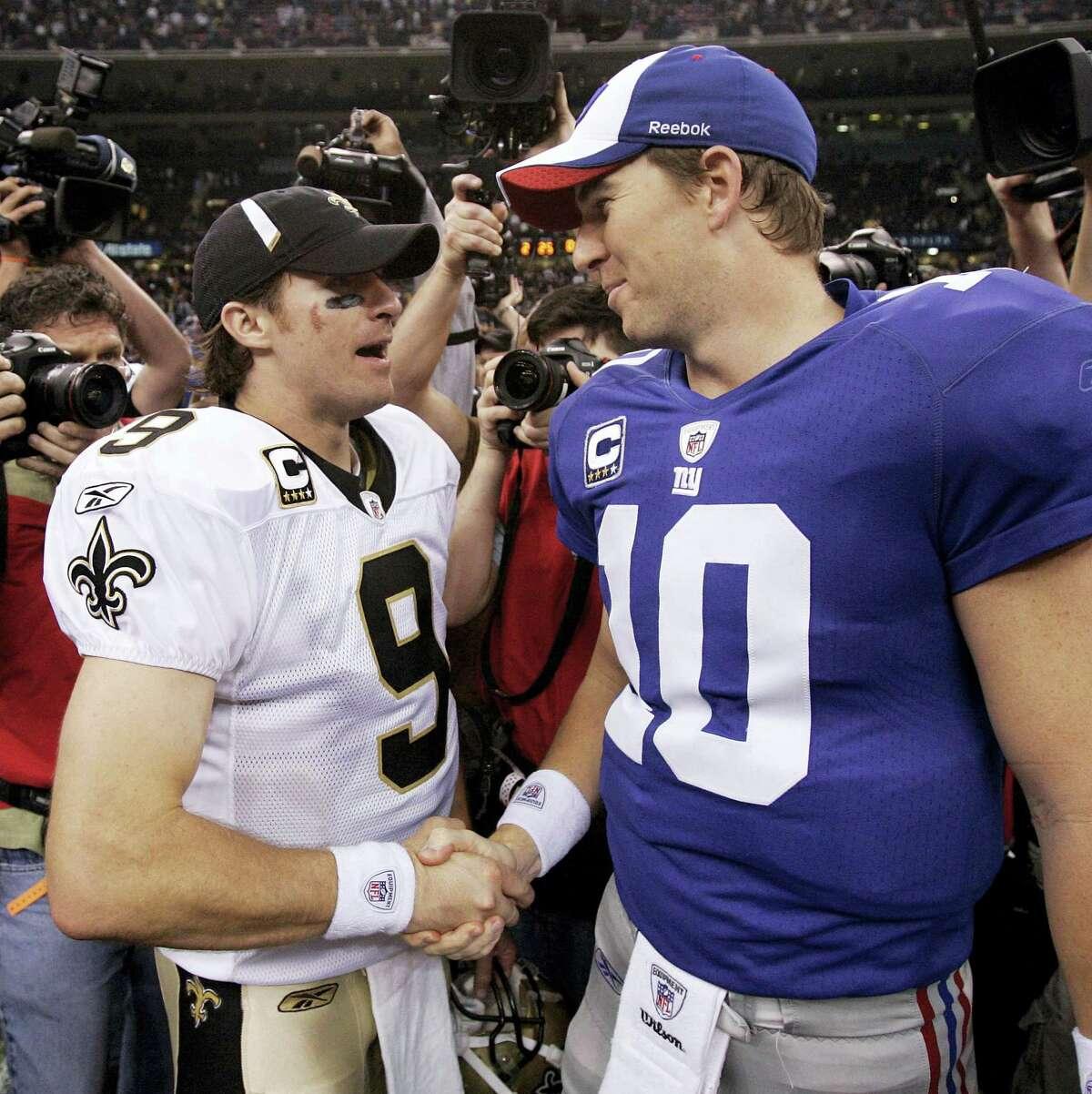 Saints quarterback Drew Brees, left, and Giants quarterback Eli Manning shake hands.
