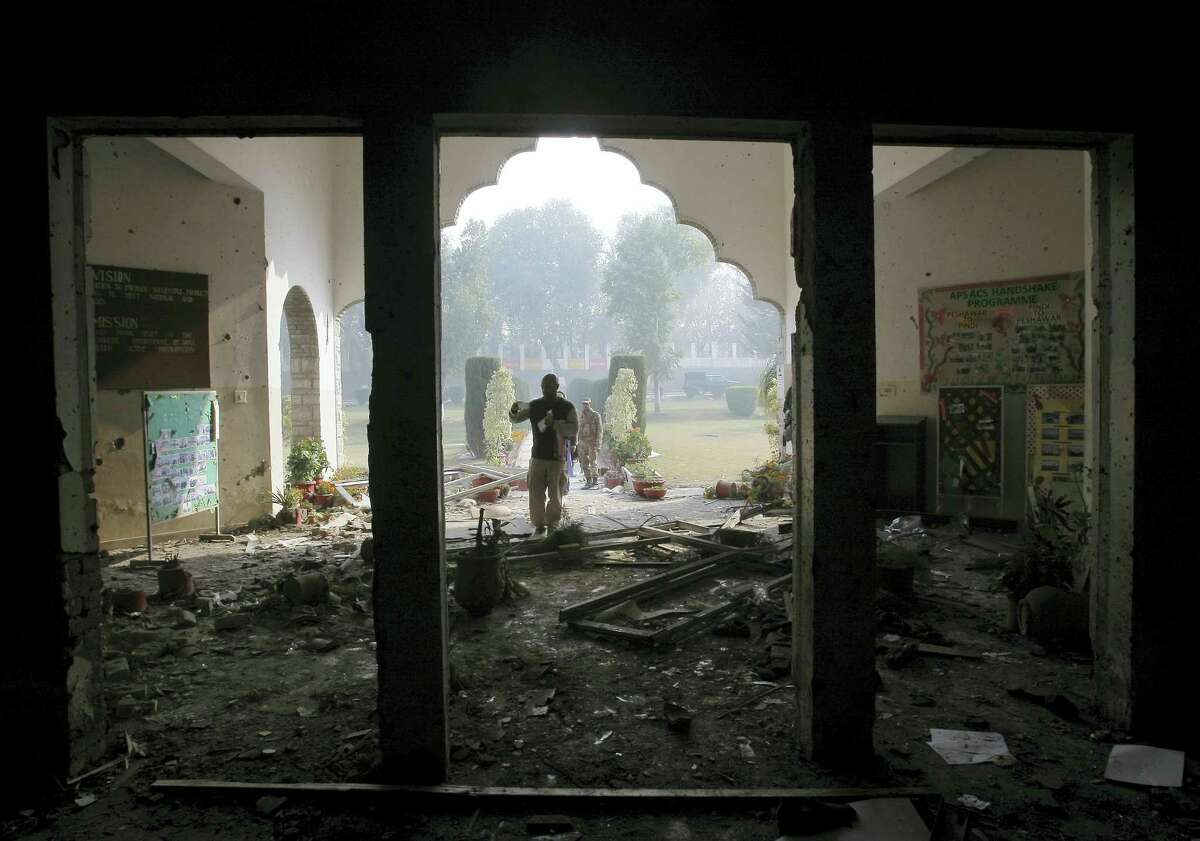 In this Dec. 17, 2014, file photo, a Pakistan army soldier inspects the Army Public School that was attacked a day before by Taliban gunmen, in Peshawar, Pakistan. The Pakistani army said Wednesday, July 13, 2016, that the mastermind of the 2014 attack on an army-run school has been killed in a U.S. drone strike. A Pakistani military spokesman says that a U.S. Army general confirmed the death of Taliban leader Khalifa Umar Mansoor in a phone call to Pakistan's army chief.