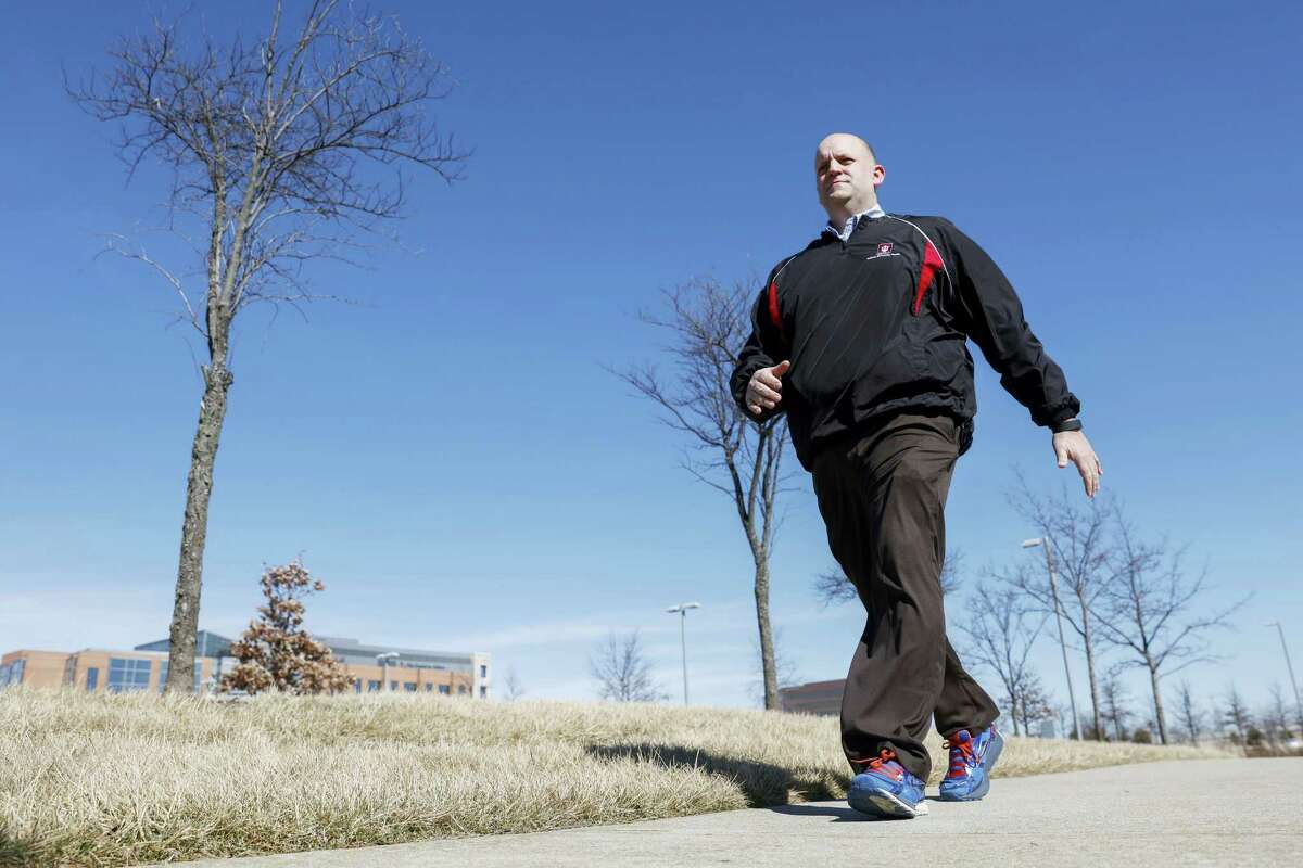 Brett Broviak, a manager of respiratory and sleep services at IU Health North Hospital, walks with his Fitbit fitness tracker on the hospital's campus in Carmel, Ind. Companies and insurers looking to reduce health-care costs are turning to incentives and may soon start rewarding you for wearing a fitness device that tracks your steps, heart rate and more.
