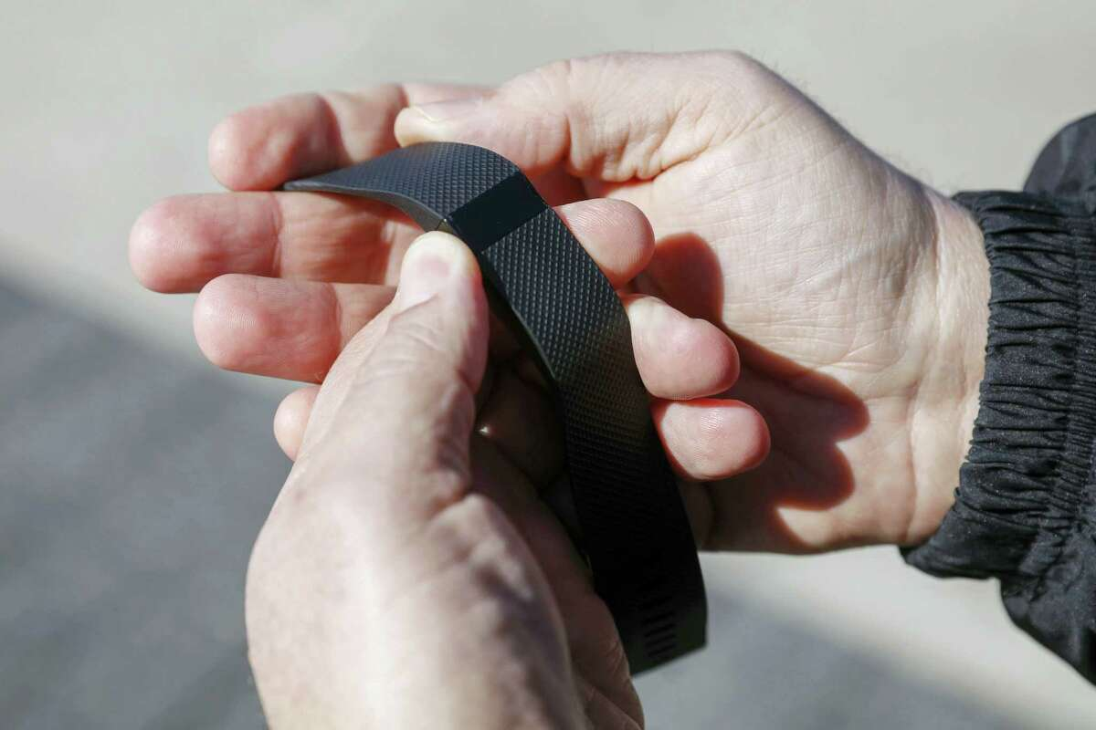 Broviak shows off his Fitbit fitness tracker for the camera on the hospital's campus in Carmel, Ind.