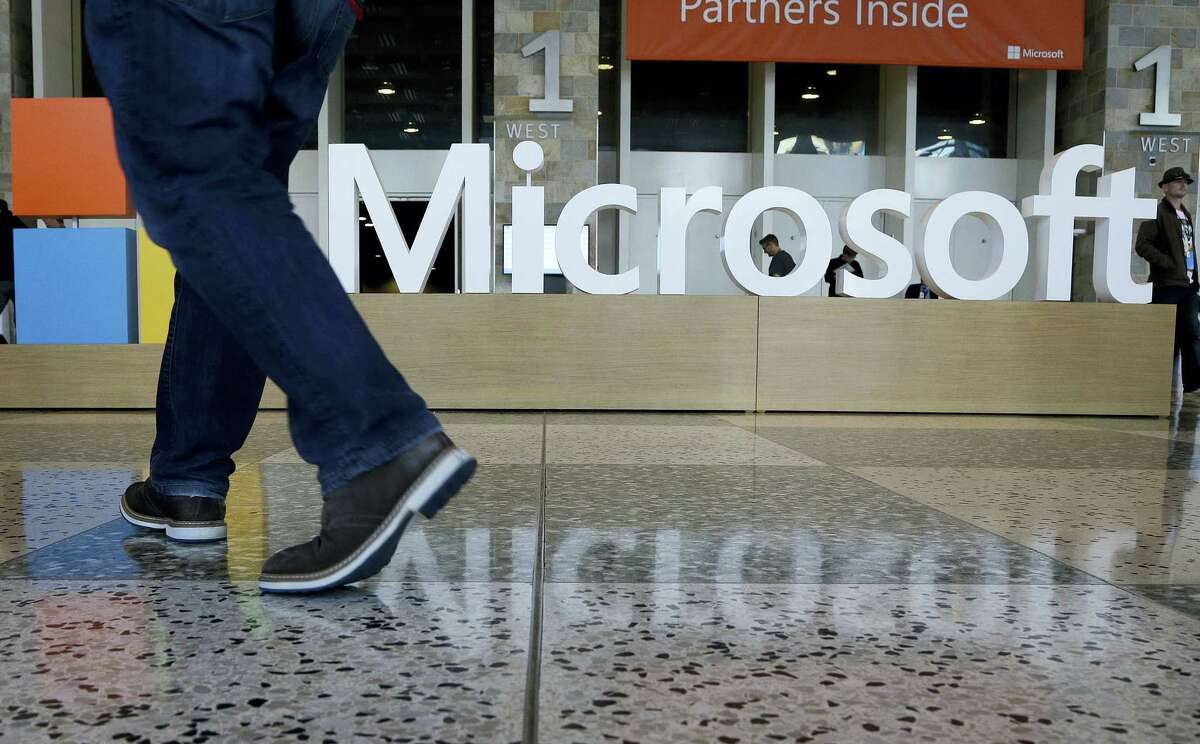 A man walks past a Microsoft sign set up for the Microsoft BUILD conference at Moscone Center in San Francisco.