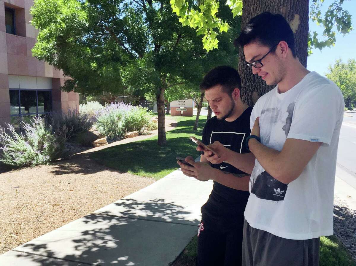 """Damien Hyatt, 23, left, and his brother, Eron Hyatt, 21, right, walk through an office park in Albuquerque in 93-degree heat on Tuesday, July 12, 2016, while playing """"Pokemon Go."""" Law enforcement agencies nationwide have issued warnings that users playing the """"augmented reality"""" game should watch where they are going and avoid trespassing on private property."""