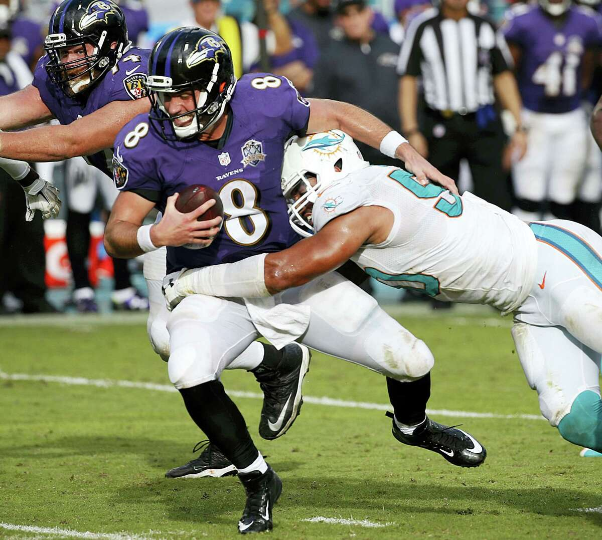FILE - In this Dec. 6, 2015, file photo, Baltimore Ravens quarterback Matt Schaub (8) is sacked by Miami Dolphins defensive end Olivier Vernon (50), during the second half of an NFL football game, in Miami Gardens, Fla. Vernon agreed to terms on what is believed to be a five-year, $85 million contract with the Giants Wednesday, March 9, 2016. (AP Photo/Wilfredo Lee, File)