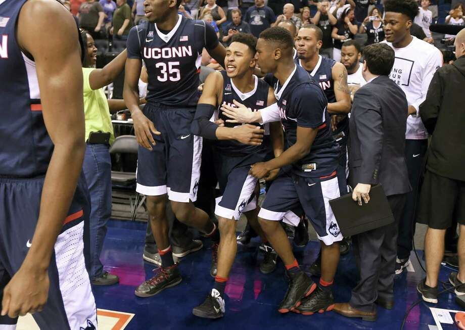 UConn players celebrate after guard Jalen Adams, center, hit a 3-pointer from beyond half court to send their AAC tournament quarterfinal game against Cincinnati into a fourth overtime in Orlando, Florida. UConn won 104-97. Photo: Brad Horrigan — Hartford Courant Via AP  / Hartford Courant