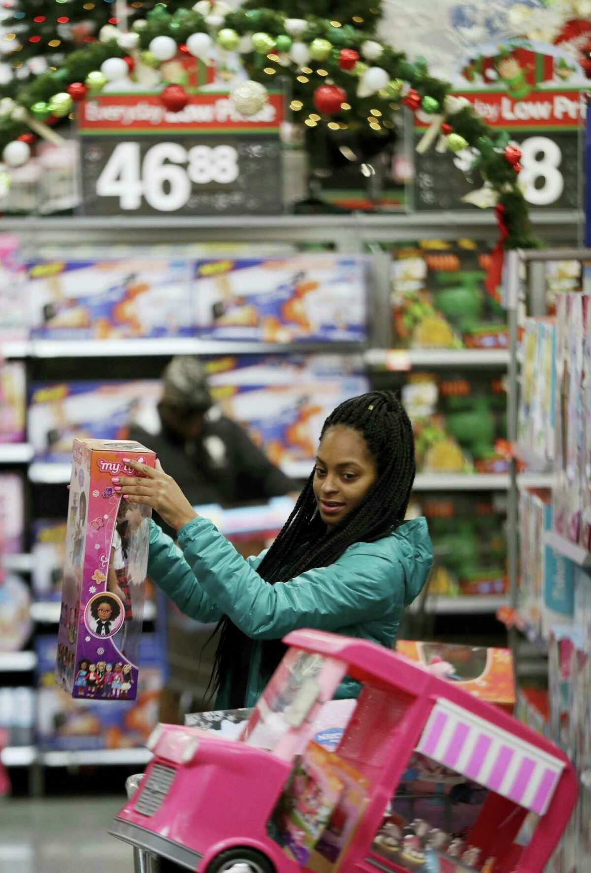 Choisette Hargon, of Paterson, N.J., shops for toys ahead of Christmas at Wal-Mart in Teterboro, N.J. It's easy to get caught up in the excitement of holiday shopping, but it's not always as easy to foot the bill. The National Retail Federation says consumers plan to spend an average of $935.58 during the holiday shopping season, which is the second highest level on record.