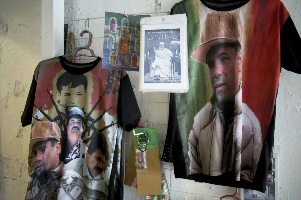 """In this photo taken Friday Oct. 16, 2015, T-shirts featuring fugitive Mexican drug lord Joaquin """"El Chapo"""" Guzman hang for sale inside the shrine of a faith healer in Mexico City, Friday, Oct. 16, 2015. The government was offering a reward of 60 million pesos, or about $3.5 million dollars, for Guzman's recapture after he made his second escape from a maximum security prison through an underground tunnel in 2015. Mexican President Enrique Pena Nieto posted on his Twitter account, Friday, Jan. 8, 2016, that Guzman has been recaptured."""