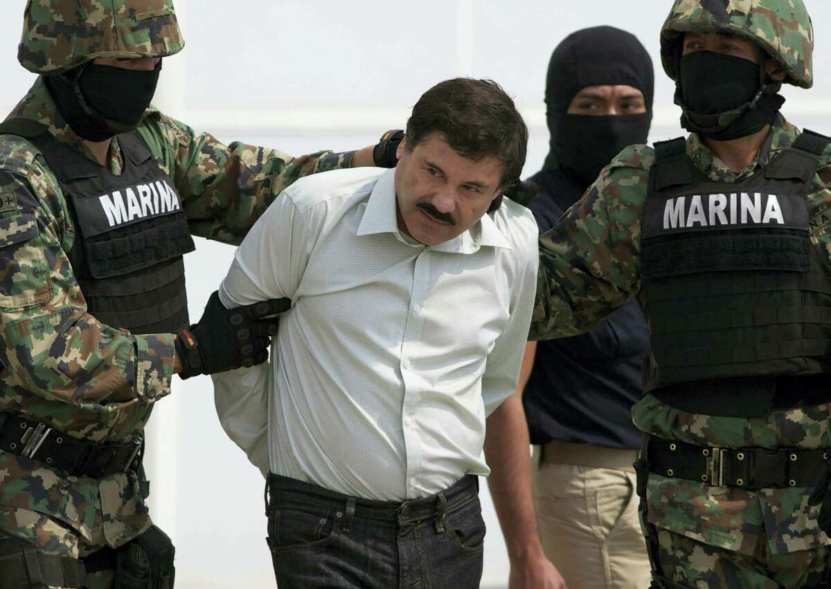 """FILE - In this Feb. 22, 2014 file photo, Joaquin """"El Chapo"""" Guzman is escorted to a helicopter in handcuffs by Mexican navy marines at a navy hanger in Mexico City, Mexico. Mexican President Enrique Pena Nieto posted on his Twitter account, Friday, Jan. 8, 2016, that drug lord Joaquin 'Chapo' Guzman has been recaptured."""