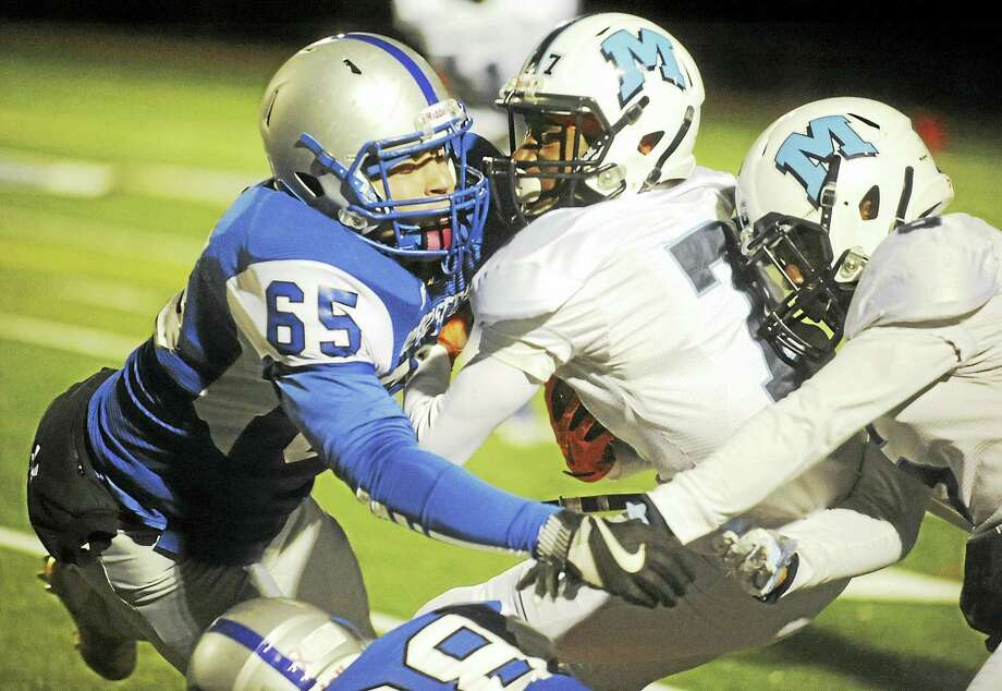 Middletown's Justin McMillian returns a punt against Bristol Eastern's Alex Acevedo (65) Friday night in Bristol. Photo: Jimmy Zanor - The Middletown Press