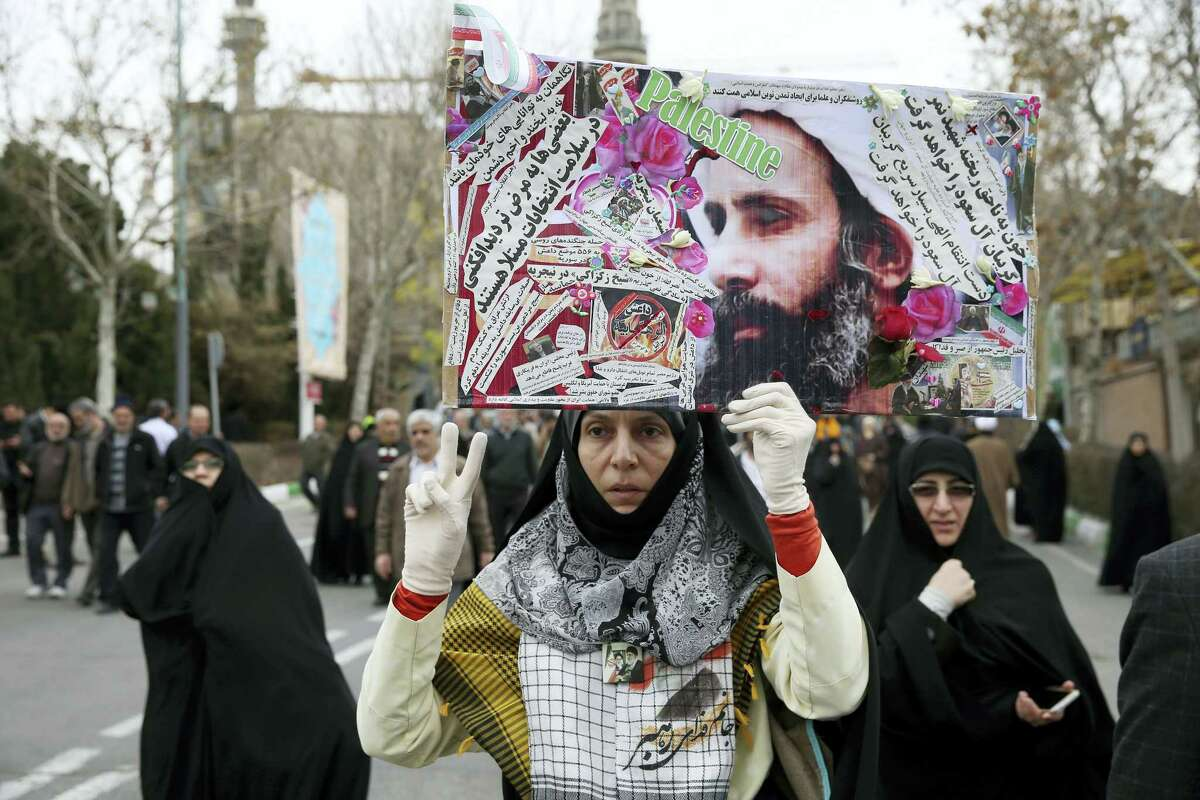 AP PHOTO — EBRAHIM NOROOZI An Iranian worshipper holds up a poster showing Sheikh Nimr al-Nimr, a prominent opposition Saudi Shiite cleric who was executed by Saudi Arabia, as she shows victory sign while attending an anti-Saudi protest rally after the Friday prayers in Tehran, Iran, Friday.
