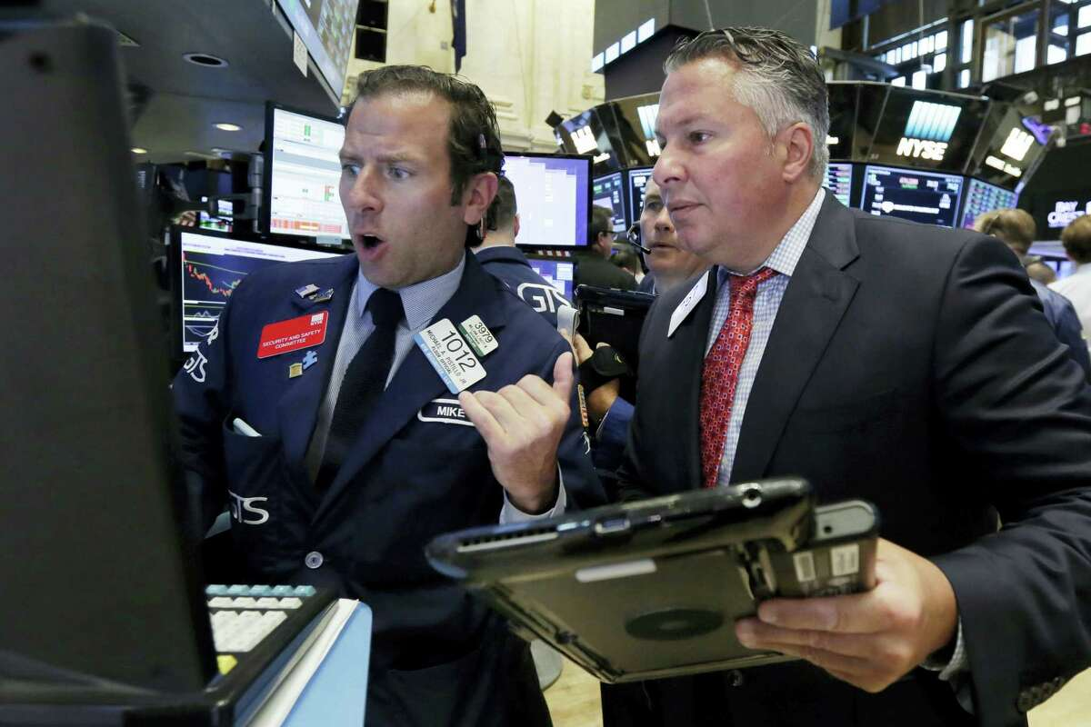 Specialist Mike Pistillo, left, and trader Mario Lagagna work on the floor of the New York Stock Exchange Wednesday.