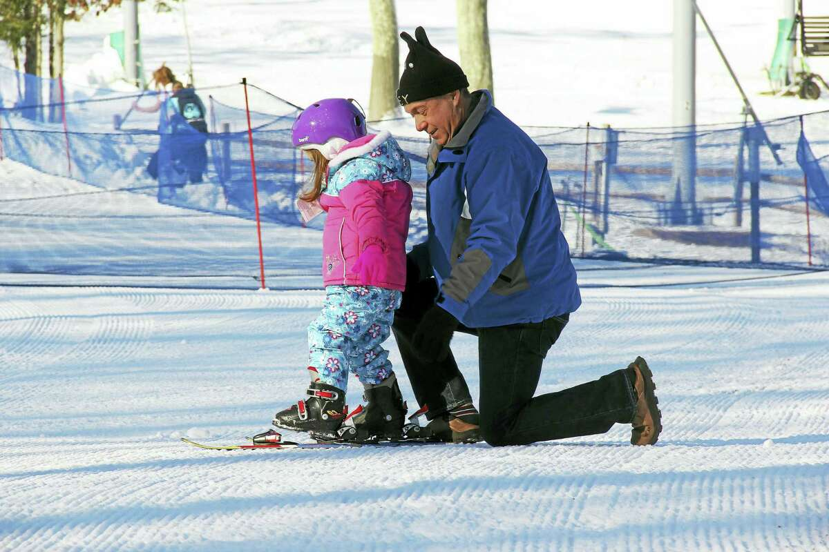 Peter Wimmer helps granddaughter Lily Wimmer, 4, attach skis for the first time Friday at Powder Ridge Mountain Park & Resort in Middlefield.