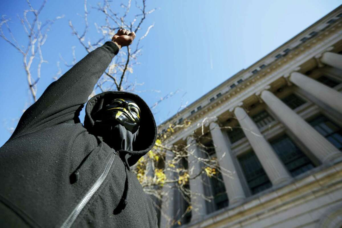 AP Photo/John Minchillo A protestor raises his fist outside the Hamilton County Courthouse after a mistrial is declared due to a hung jury in the murder trial against Ray Tensing, Saturday, Nov. 12, 2016, in Cincinnati. Tensing, a white former University of Cincinnati police officer, was charged with murder in the shooting of Sam DuBose, an unarmed black motorist, while on duty during a routine traffic stop on July 19, 2015.