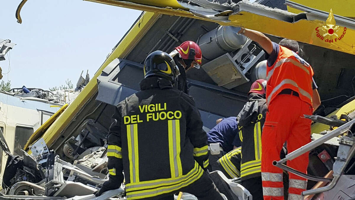 Italian firefighters Vigili del Fuoco inspect the wreckage of two commuter trains after their head-on collision in the southern region of Puglia, killing several people on July 12, 2016.