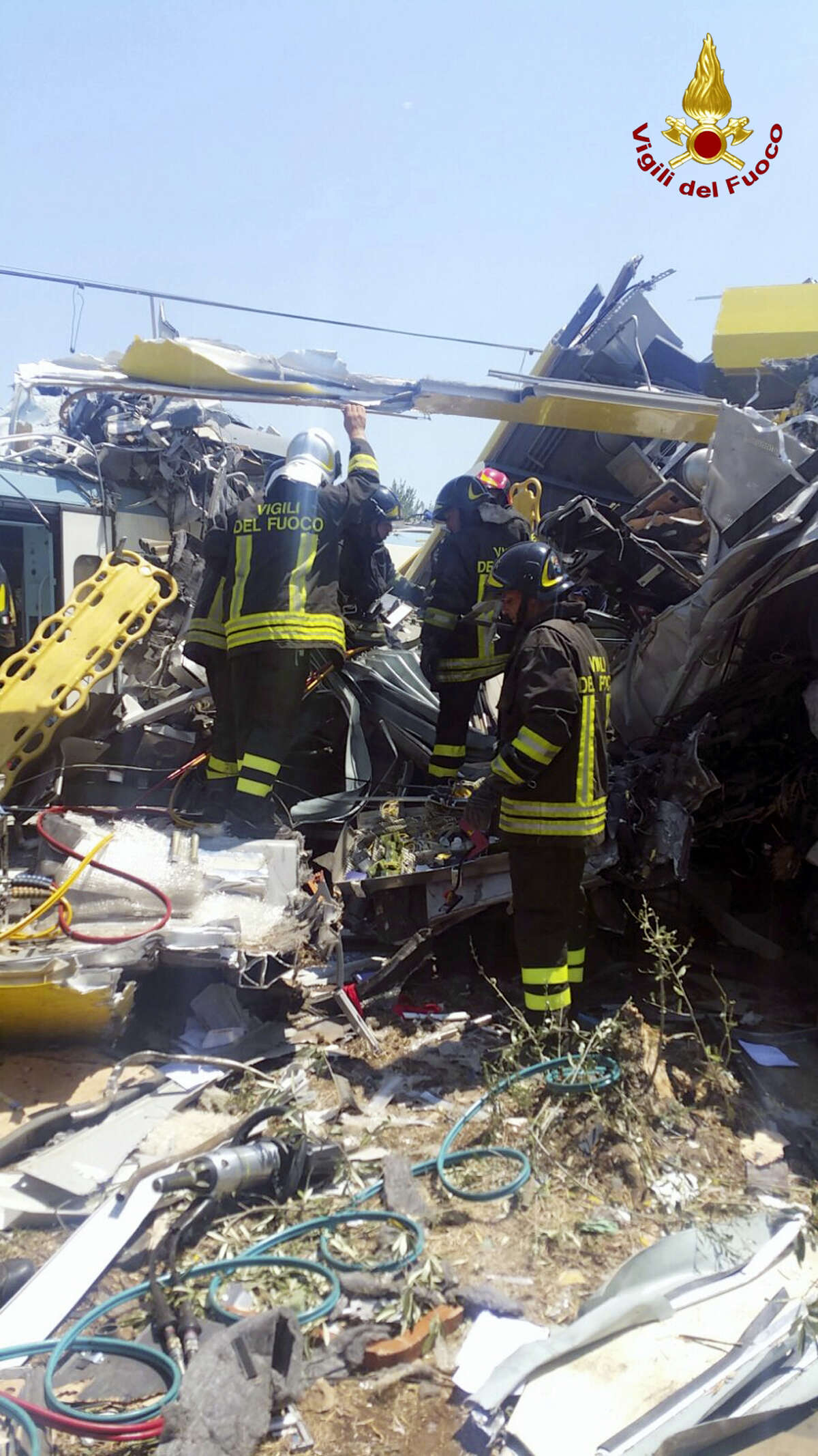 Italian firefighters perform rescue operations at the scene of a train accident after two commuter trains collided head-on near the town of Andria, in the southern region of Puglia, killing several people on July 12, 2016.