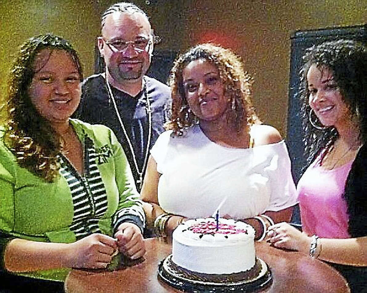 New Britain Social Worker Kally Moquete (far right) celebrates recently with her foster family, including (from left) sister Tyanna Arroyo, father Ricardo Arroyo and mother Giovanna Francisco. After becoming a foster parent to Moquete, Francisco went on to complete her studies and became a social worker.