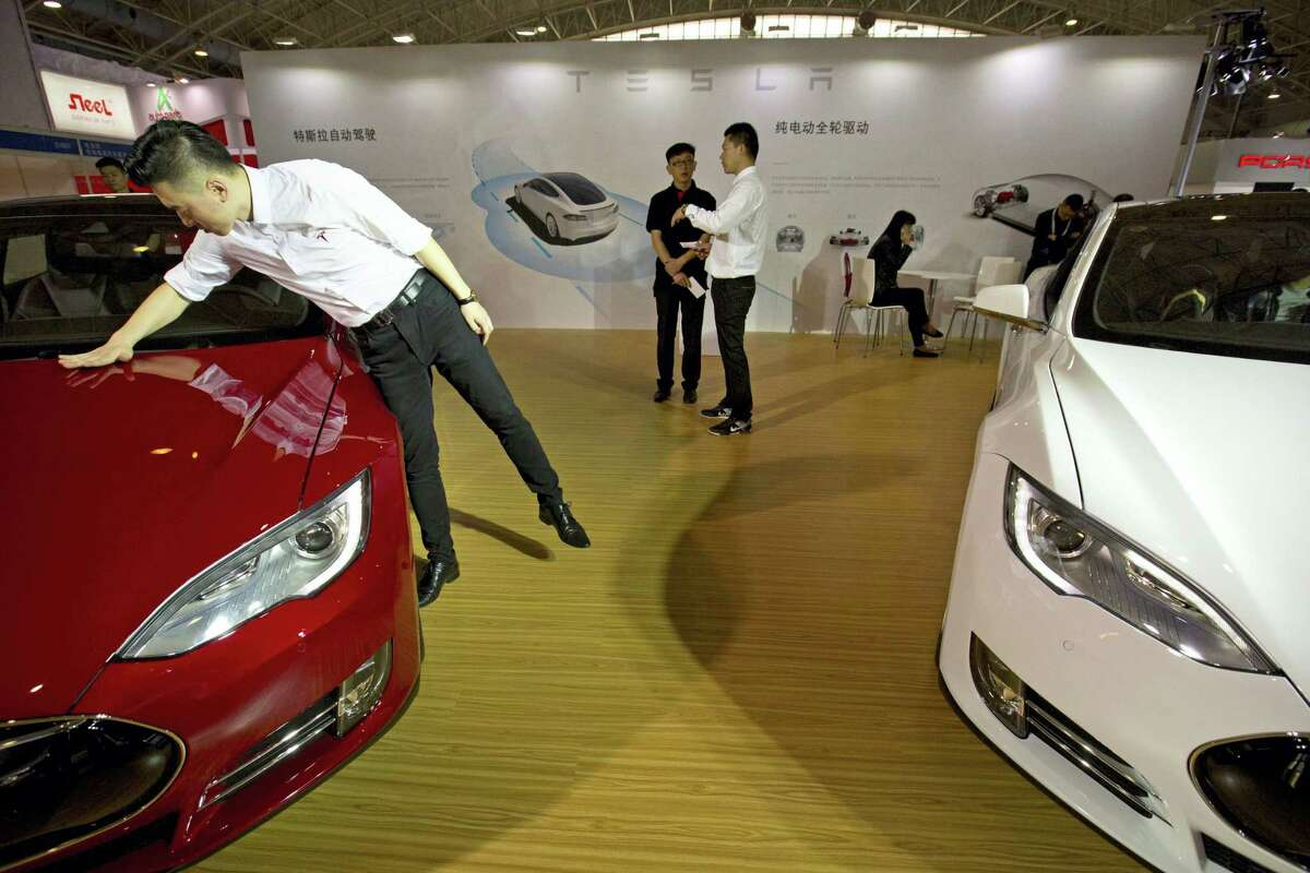In this April 25, 2016 photo, a staff member cleans the hood of a Tesla Model S electric car near a display advertising Tesla's self-driving features at the Beijing International Automotive Exhibition in Beijing, China.