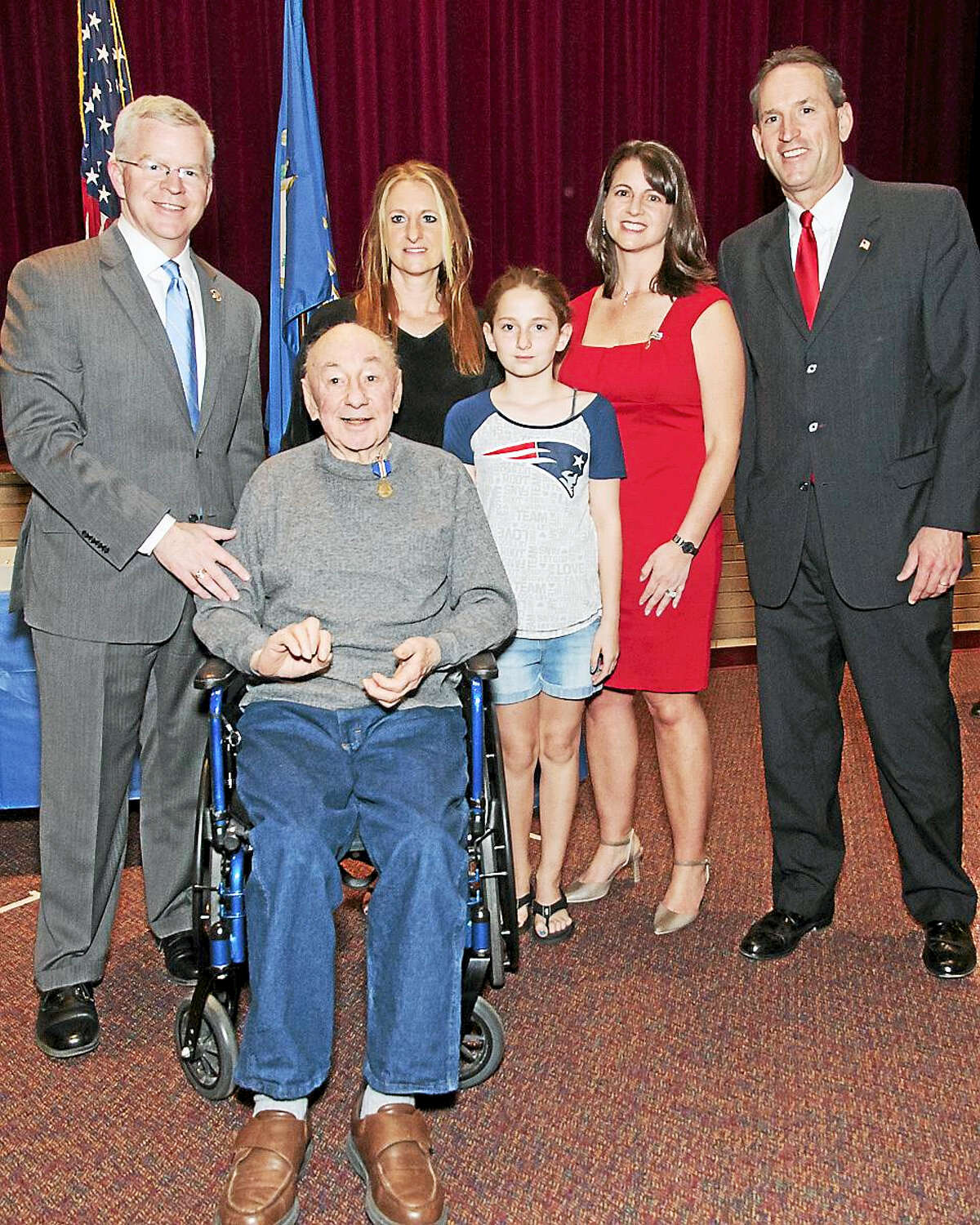 Veteran Richard Lucco poses with family and Department of Veterans' Affairs Commissioner Sean Connolly, state Rep. Christie Carpino and state Sen. Paul Doyle after being presented with the Connecticut Wartime Service Medal at a ceremony at Cromwell Middle School.