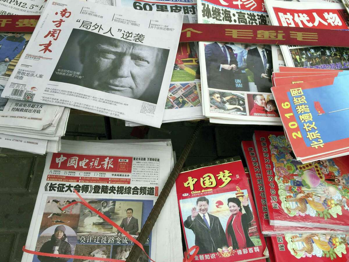 """A front page of a Chinese newspaper with a photo of U.S. President-elect Donald Trump and the headline """"Outsider counter attack"""" is displayed at a newsstand in Beijing, China, Thursday."""
