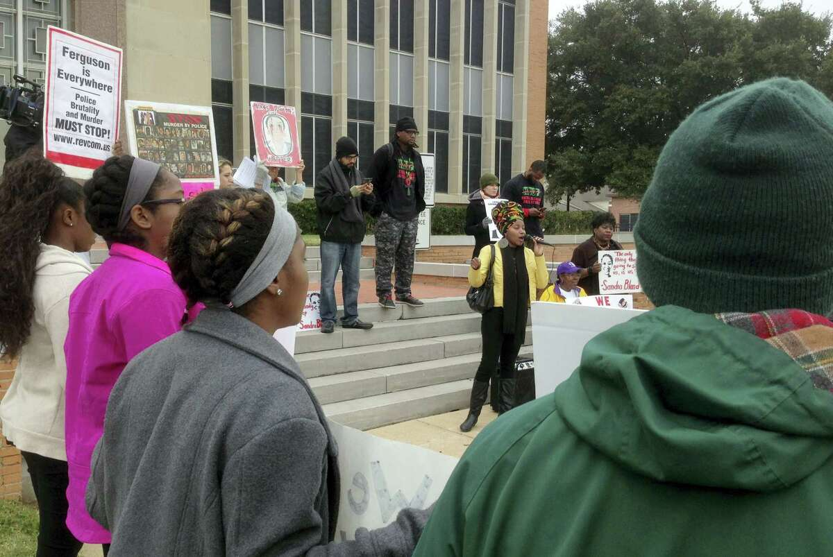 About two dozen people demonstrate outside the Waller County Courthouse on Wednesday, Jan. 6, 2016, in Hempstead, Texas. A grand jury has resumed considering the case of Sandra Bland, the black Chicago-area woman who died in a Texas county jail three days after her arrest in a traffic stop last summer.