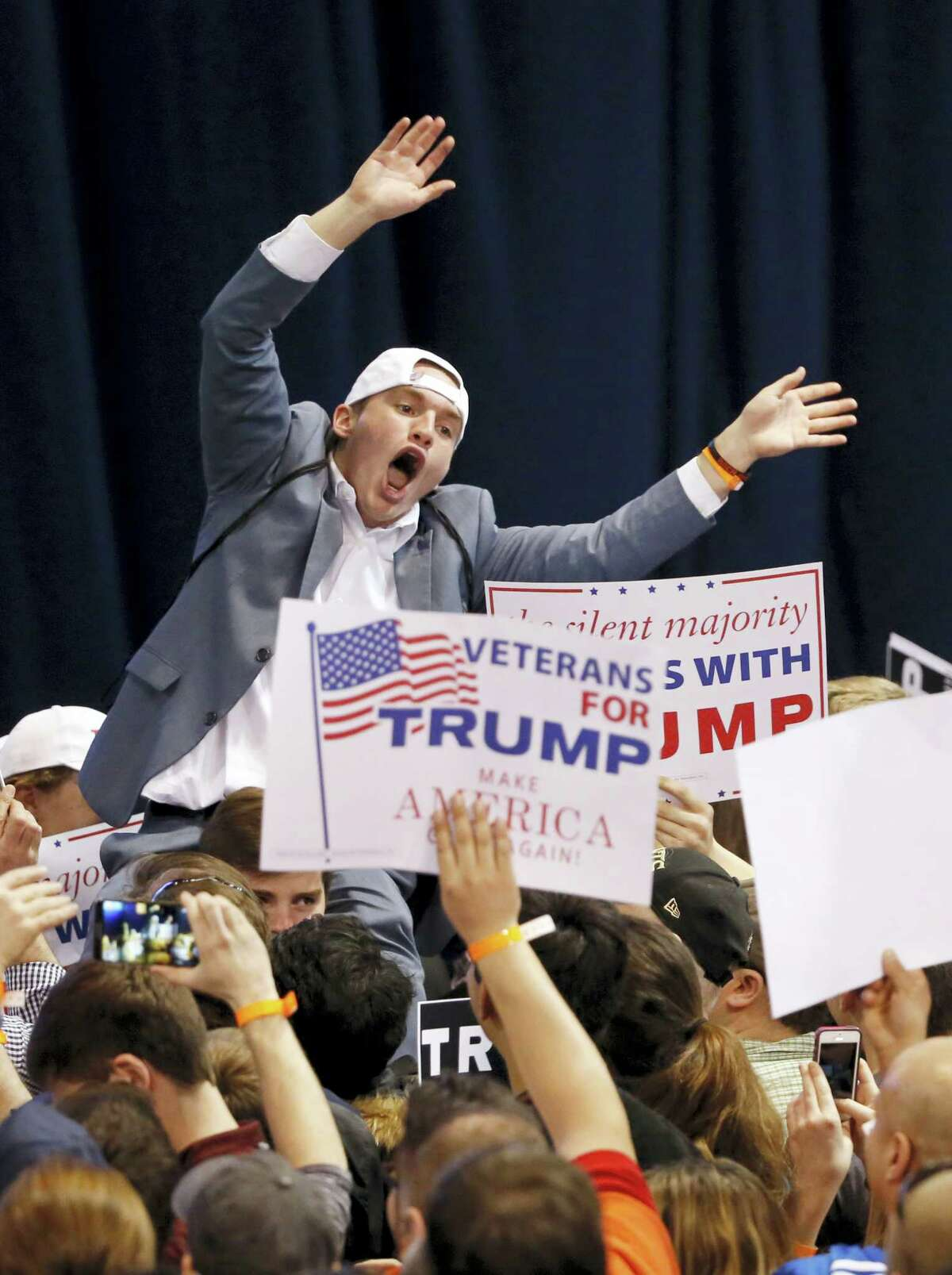 A supporter of Republican presidential candidate Donald Trump tries to pump up the crowd before it was announced the rally had been canceled on the campus of the University of Illinois-Chicago, Friday, March 11, 2016, in Chicago.