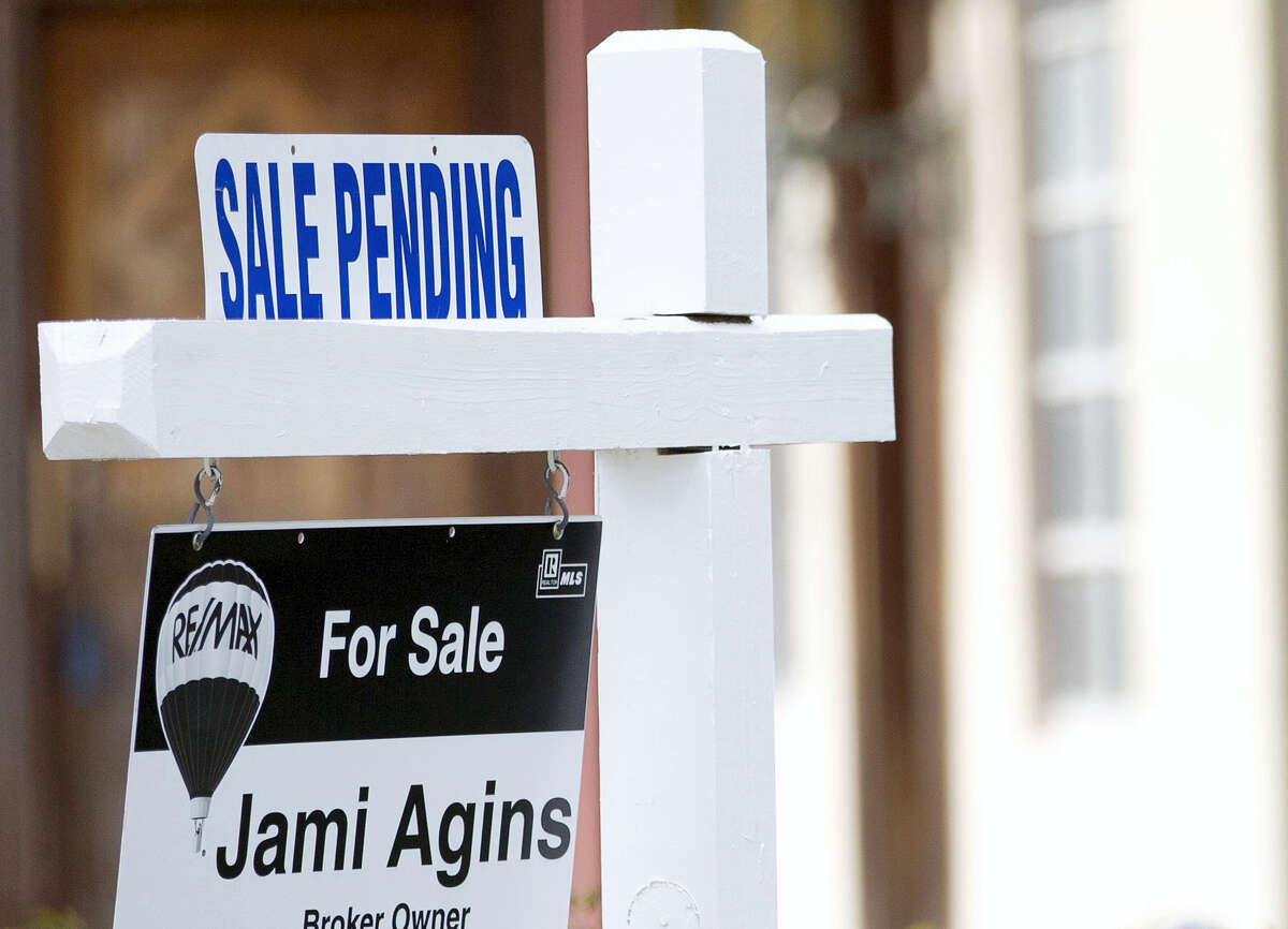 """A """"Sale Pending"""" sign sits atop a realty sign outside a home for sale in Surfside, Fla."""
